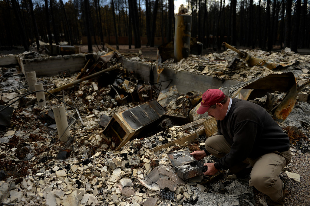 Description of . COLORADO SPRINGS, CO. - June 18: Ted Robertson finds boxes of burned papers in the rubble as he sifts through the damage to his home that was totally taken by the fire as some residents were allowed back to see their homes in the Black Forest Fire area near Colorado Springs, Colorado. June 18, 2013. Colorado Springs. (Photo By Joe Amon/The Denver Post)