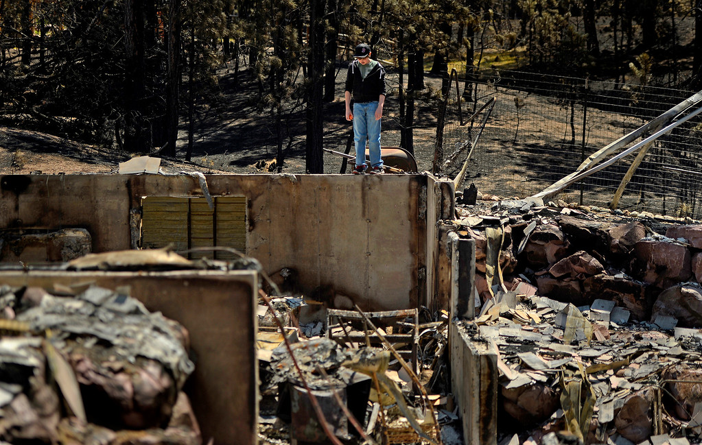 Description of . Nolan Schultz, 16, stands amid the ruins of his destroyed home on June 19, 2013. After being evacuated for about a week, his family was allowed to return to the area to view the damage.
