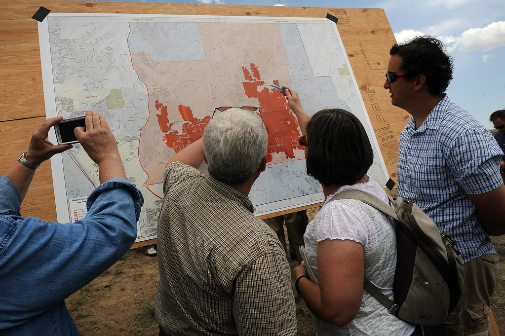 Description of . Black Forest evacuees look at a map of the perimeter of the Black Forest Fire after a press briefing about the Black Forest Fire held for members of the media and for homeowners at Pikes Peak Community College Rampart Range Campus near Monument, CO  on June 15, 2013.  Photo by Helen H. Richardson/The Denver Post)
