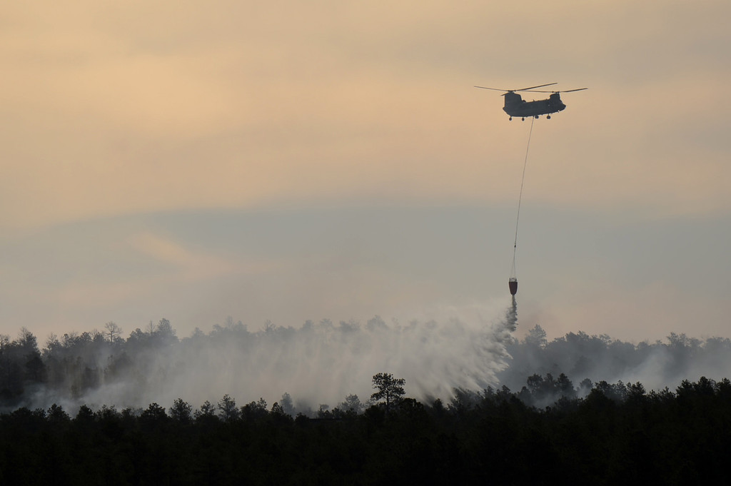 Description of . COLORADO SPRINGS, CO. - June 12: A helicopter makes a water drop on the midst of the Black Forest Fire. Colorado Springs, Colorado. June 12, 2013. (Photo By Hyoung Chang/The Denver Post)