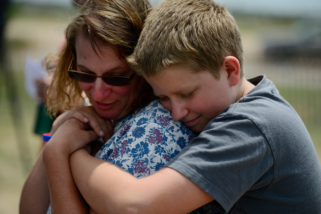 Description of . COLORADO SPRINGS, CO - JUNE 18: Kim Redus is hugged by her son Zach, 12, as they listen during a press conference held by the El Paso County Sheriff to inform residents of their re-admittance status. Residents in Cathedral Pines were allowed in by 2 p.m., while residents between Vollmer and Herring Roads and Black Forest and Herring Roads both locations between Shoup Road and Kirk Road north-south will be allowed in for three hours. (Photo by AAron Ontiveroz/The Denver Post)