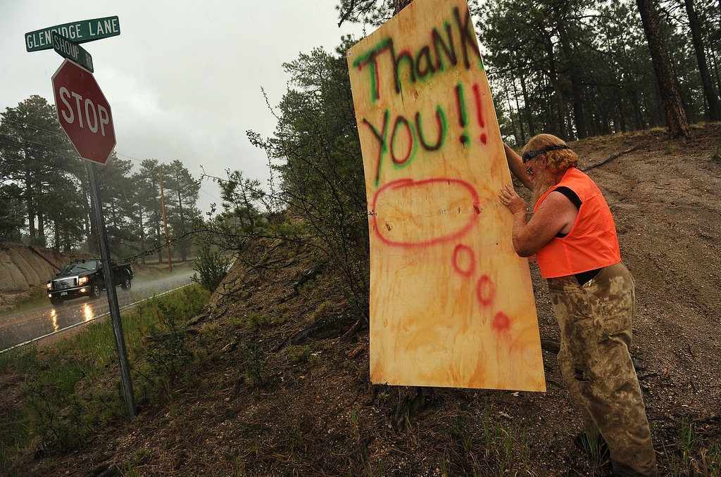 Description of . BLACK FOREST, CO - JUNE 17:   Amidst a downpour of rain and hail, Black Forest resident Mike Turner puts out a sign saying Thank You to all the firefighters whom he called absolute heroes along Shoup Road in Black Forest, CO on June 17, 2013.  Turner never evacuated from the fire and tried to save his mother\'s house and property.  His mother, who is 90 years old, has lived in the Black Forest for 49 years.  She lost everything in the fire.    Photo by Helen H. Richardson/The Denver Post)