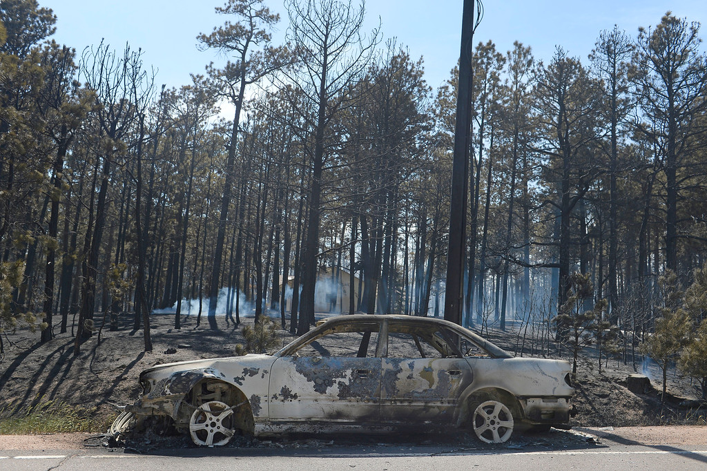 Description of . COLORADO SPRINGS, CO - JUNE 12: A car parked along Black Forest Road is destroyed by the Black Forest Fire on June 12, 2013.  The Black Forest Fire continues to burn and high winds are expected throughout the rest of the day.  Photo by Helen H. Richardson/The Denver Post)