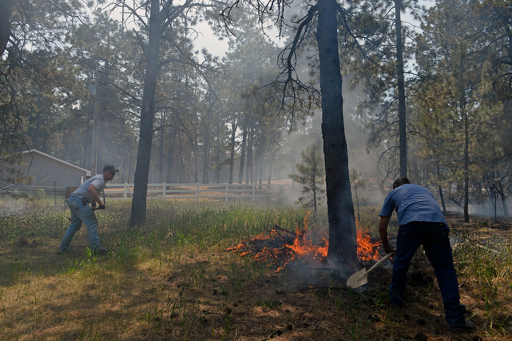 Description of . COLORADO SPRINGS, CO - JUNE 12:  Matt Newland, left, and friend Chad Mazari take shovels in around neighbors houses to help put out small fires off of Cyprus road in the Black Forest on June 12, 2013. He and his friend Matt Newland stayed close to their house on Herring Road to make sure they could watch the fire to protect their house.  They had all of their belongings ready to go and an escape route in place in case they need to leave. So far the fire has moved east of their house, but the Black Forest fire continues to burn and has yet to have any containment.   Photo by Helen H. Richardson/The Denver Post)