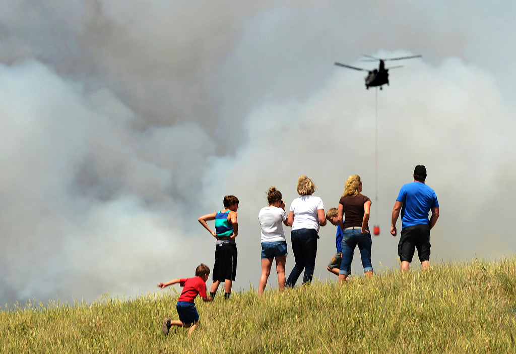 Description of . People climb a hill to watch helicopters gather water to dump on the Black Forest fire on June 12, 2013. According to El Paso County Sheriff Terry Maketa, the Black Forest fire, north of Colorado Springs, had already burned 80-100 homes.