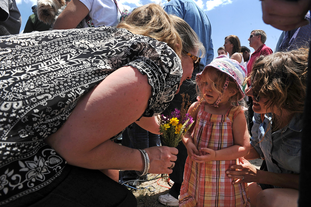Description of . 2 year old  Saylor Brown gives flowers to Black Forest fire evacuee Cheryl Carden, during a press briefing about the Black Forest Fire held for members of the media and for homeowners at Pikes Peak Community College Rampart Range Campus near Monument, CO  on June 15, 2013. Carden knows that she lost her home in the fire. Brown\'s aunt Rebecca Abernathy is at right.  Photo by Helen H. Richardson/The Denver Post)