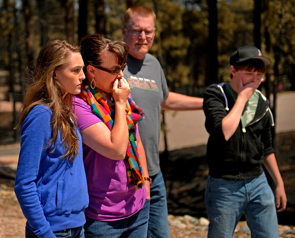 Description of . The Schultz family - from left, Annissa, 20, mother Camla, father Mike and brother Nolan, 16 - look at their destroyed home for the first time as residents were allowed to return to the Black Forest fire burn zone on June 19, 2013. The family had lived in the house for eight years. The family\'s home was one of 509 houses destroyed in the fire.