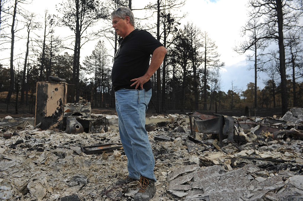 Description of . BLACK FOREST, CO - JUNE 18:  Robert Runyard surveys what is left of his home on Swan Road in Black Forest, CO on June 18, 2013.  Runyard and his girlfriend Amy Feik, not pictured, returned home for the first time to their home on Swan Road in Black Forest, CO on June 17, 2013.  Residents of Black Forest were finally allowed back into their burned homes for the first time since the fire devoured thousands of acres inside the Black Forest taking with it 502 homes and two lives.  Photo by Helen H. Richardson/The Denver Post)