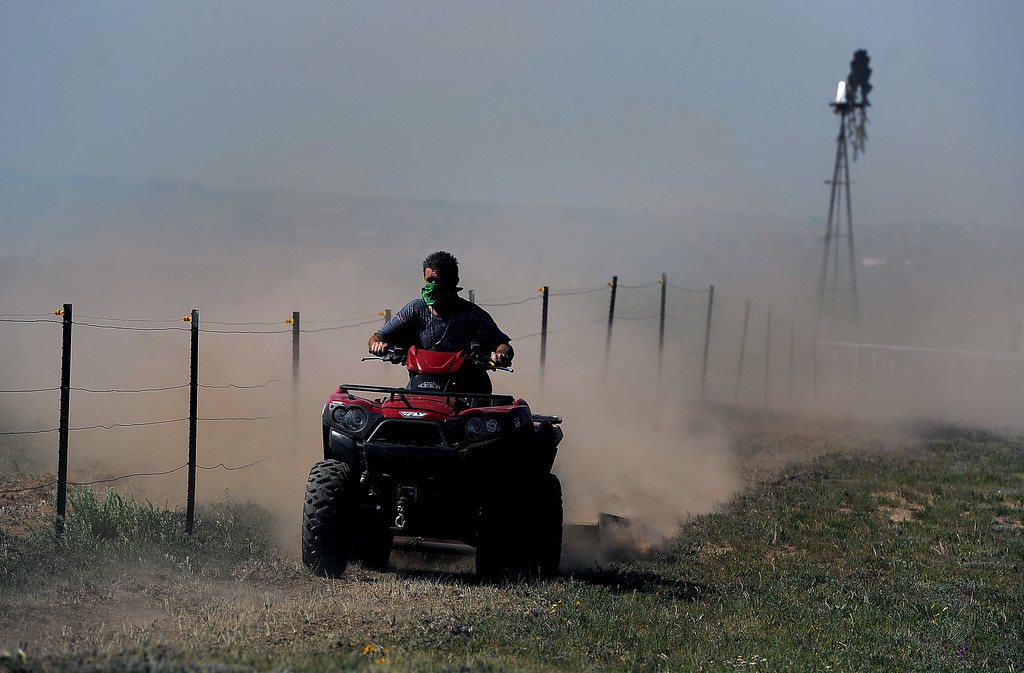 Description of . COLORADO SPRINGS, CO - JUNE 12: Using an ATV with a grader on the back a homeowner work aggressively to create a fire line around his ranch just off of Black Forest Road to save it from the Black Forest Fire in the Black Forest on June 12, 2013.   Photo by Helen H. Richardson/The Denver Post)