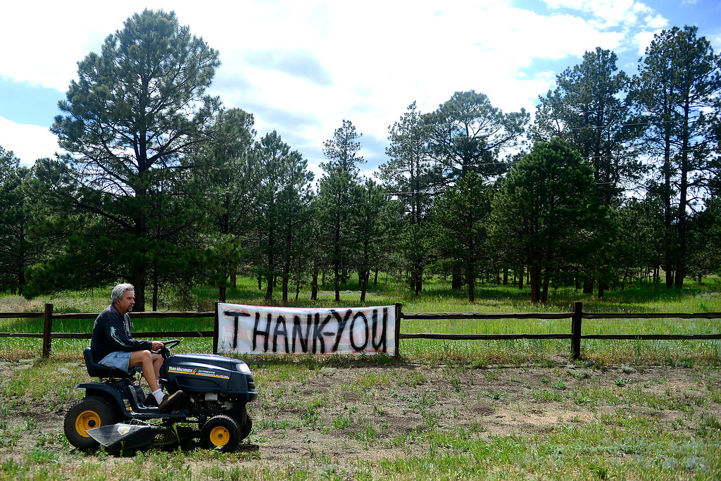 Description of . COLORADO SPRINGS, CO - JUNE 17: Kevin Kline, a resident of Highway 83 south of Hodgen Road, mows his grass as a precautionary measure to protect his home in the event that another fire hits the area. Kline, along with his wife and 10 dogs, was among those evacuated last week as the Black Forest Fire grew. (Photo by AAron Ontiveroz/The Denver Post)