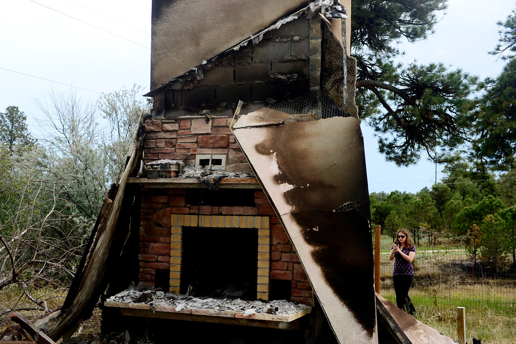 Description of . COLORADO SPRINGS, CO - JUNE 18: Audrea Branham photographs a chimney at a rental property owned by Jesse Russow, which was the southernmost home burned on the west side of Vollmer Road. The occupant of the home, who was not named, was only able to save himself and his motorcycle as he was away from the property when the evacuation took place. Russow is accepting donations for fire crews at 7195 Templeton Gap Road in Colorado Springs. (Photo by AAron Ontiveroz/The Denver Post)