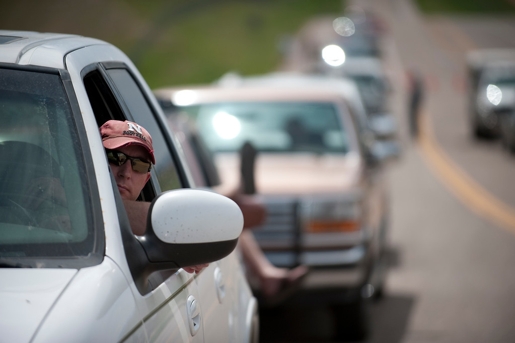 Description of . Ty Ruter waits in line at Highway 83 and Hodgen Road to be escorted to his home in Black Forest by police on Saturday, June 15, 2013. (Photo By Grant Hindsley / The Denver Post)