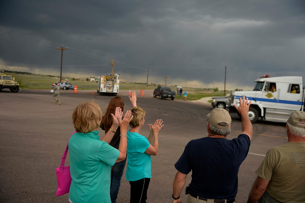 Description of . COLORADO SPRINGS, CO. - June 14: Residents wave and clap at passing firefighters as they wait for their escourt into the Black Forest Fire area to quickly get medications and important items that were left behind in the rush to evacuate near Colorado Springs, Colorado. June 14, 2013 Denver, Colorado Springs. (Photo By Joe Amon/The Denver Post)