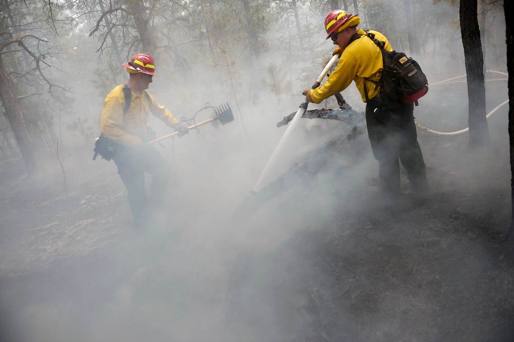 Description of . 1st Sgt John Screiber, left, helps put out fire while Sgt David Meggison, right puts water on hotspots  on property along Winchester Road north of Hodgen Road in the midst of the Black Forest Fire on June 13, 2013.  Photo by Helen H. Richardson/The Denver Post)