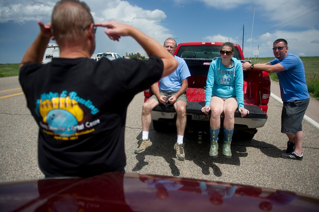 Description of . Mike Perry, left, tells a story from his days in the military to John Adamson, his daughter, Heather Stanley, and her husband Shawn Stanley, while waiting in line to be escorted to their respective homes in Black Forest on Saturday, June 15, 2013. Police were only letting residents in, with proof of residence, for pets or medications.  (Photo By Grant Hindsley / The Denver Post)