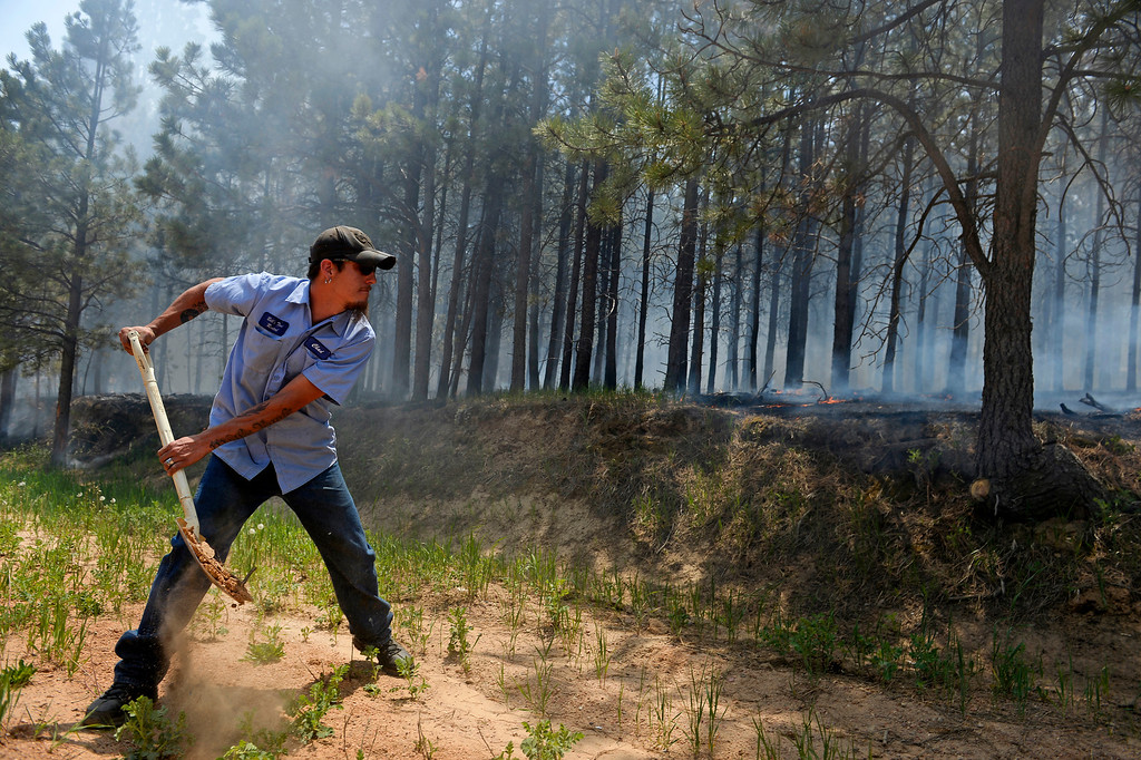 Description of . COLORADO SPRINGS, CO - JUNE 12:  Chad Mazari helps to put dirt on active fire around neighbors houses off of Cyprus road in the Black Forest on June 12, 2013. He and his friend Matt Newland stayed close to their house on Herring Road to make sure they could watch the fire to protect their house.  They had all of their belongings ready to go and an escape route in place in case they need to leave. So far the fire has moved east of their house, but the Black Forest fire continues to burn and has yet to have any containment.   Photo by Helen H. Richardson/The Denver Post)