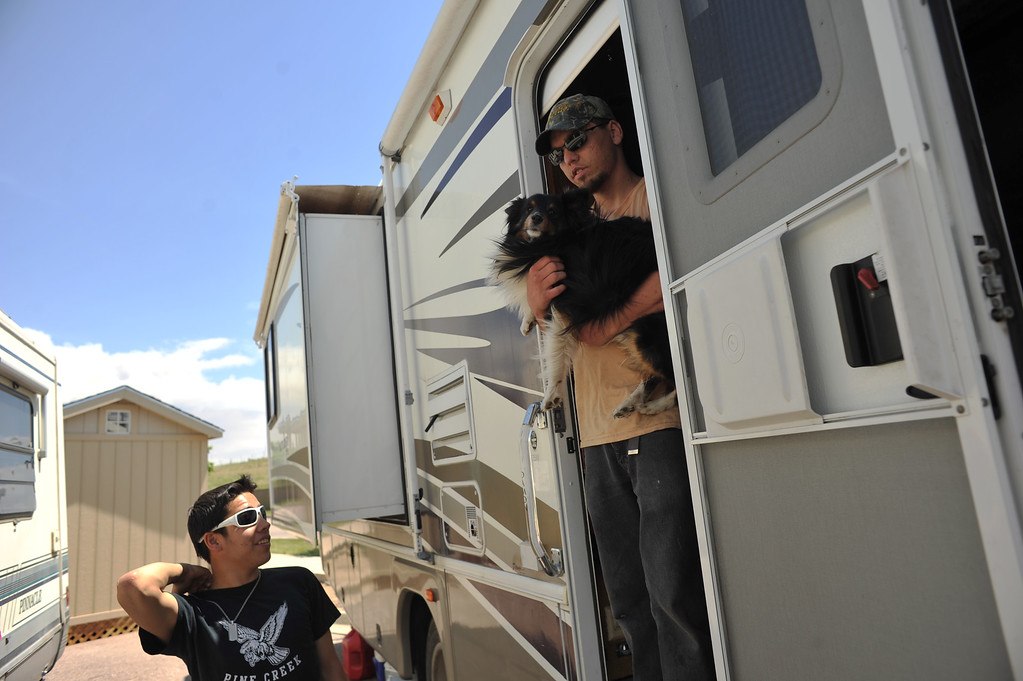 Description of . COLORADO SPRINGS, CO. - June 12: Black Forest Fire evacuees Talon, 15, left, and Alex, 24, takes care of the dog at the parking of Walmart in Colorado Springs. Colorado Springs, Colorado. June 12, 2013. Their foster parents Deborah and her husband Larry and 6 other foster children and 4 dogs spend over night at the parking. (Photo By Hyoung Chang/The Denver Post)