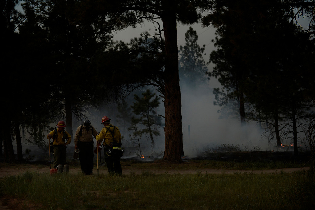 Description of . COLORADO SPRINGS, CO. - June 13: Firefighters refill their burn cans after back burning at Black Forest trail head section 16 near the corner of Burgess Rd and Buckskin Ln along the edge of the Black Forest Fire Colorado Springs, Colorado. June 13, 2013 Denver, Colorado Springs. (Photo By Joe Amon/The Denver Post)