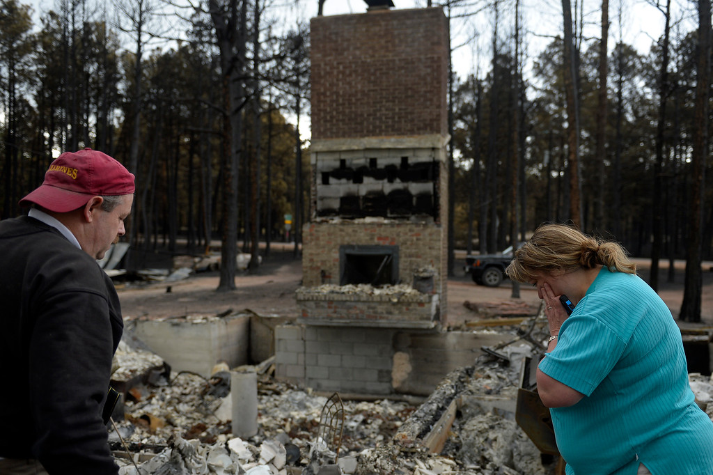 Description of . COLORADO SPRINGS, CO. - June 18: Ted and Teresa Robertson\' look over their home that was totally taken by the fire as some residents were allowed back to see their homes in the Black Forest Fire area near Colorado Springs, Colorado. June 18, 2013. Colorado Springs. (Photo By Joe Amon/The Denver Post)