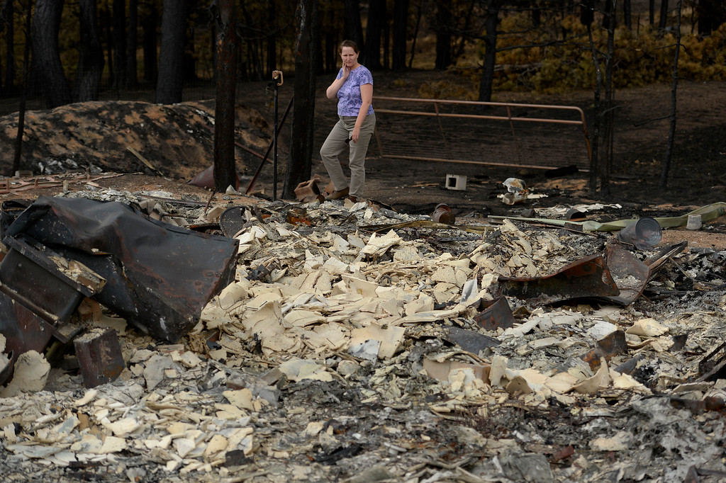 Description of . BLACK FOREST, CO - JUNE 18:  Amy Feik walks the grounds of what was  home she shared with boyfriend Robert Runyard in Black Forest, Co on June 18, 2013.  Feik and Robert Runyard, not pictured, returned home for the first time to their home on Swan Road in Black Forest, CO on June 17, 2013.  Residents of Black Forest were finally allowed back into their burned homes for the first time since the fire devoured thousands of acres inside the Black Forest taking with it 502 homes and two lives.  Photo by Helen H. Richardson/The Denver Post)