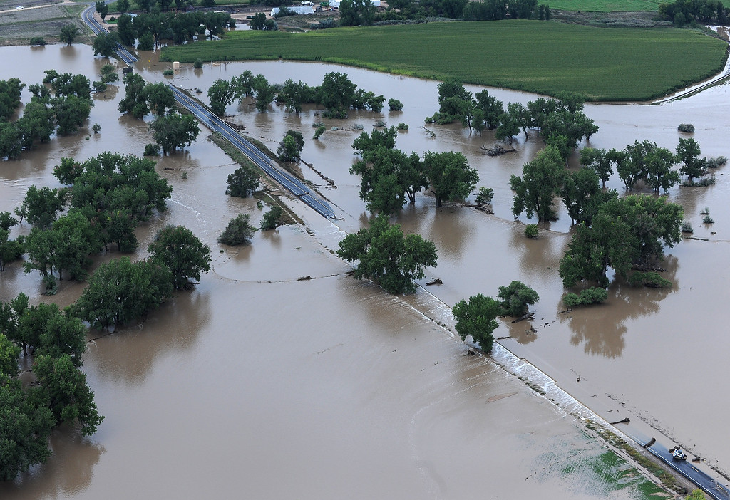Description of . Flood water from the Big Thompson River flows over County Road 27 1/2 in Weld County on Monday, September 16, 2013. (Photo By Tim Rasmussen/The Denver Post)