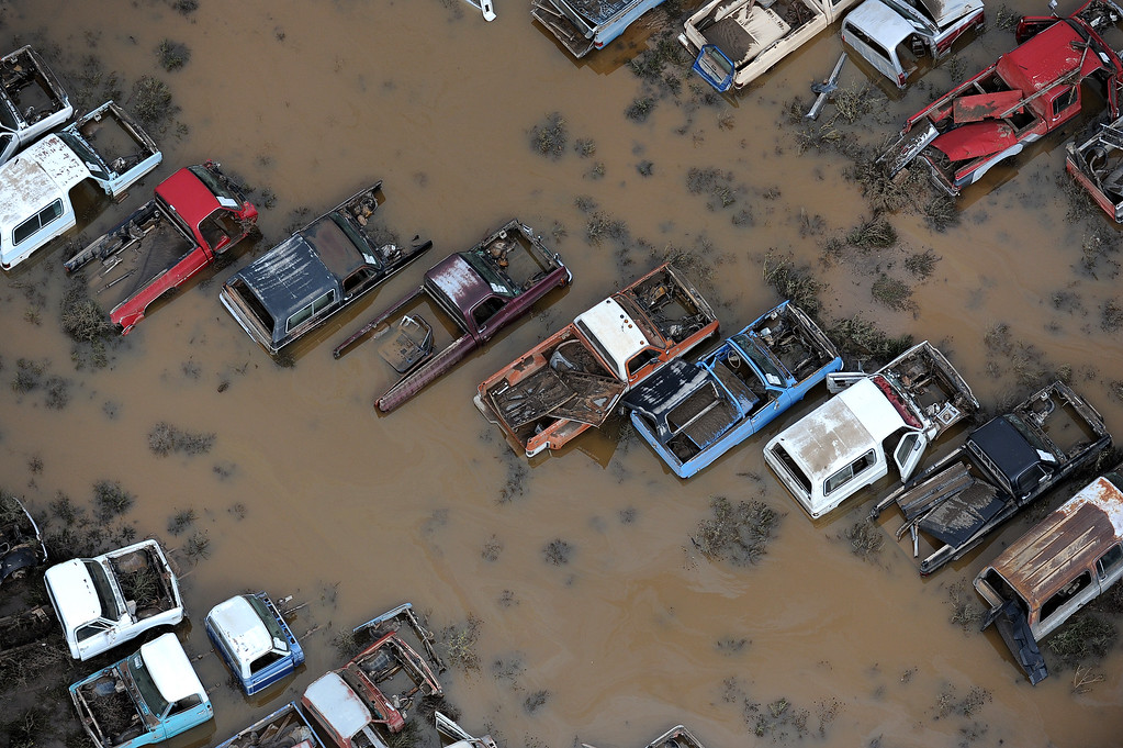 Description of . Cars in a junk yard on 37th Street in Evans,  Colorado, are surrounded by flood waters and mud from the Platte River in Weld County on Monday, September 16, 2013. The flood has devastated cities and farms throughout the county and elsewhere in the state. (Photo By Tim Rasmussen/The Denver Post)