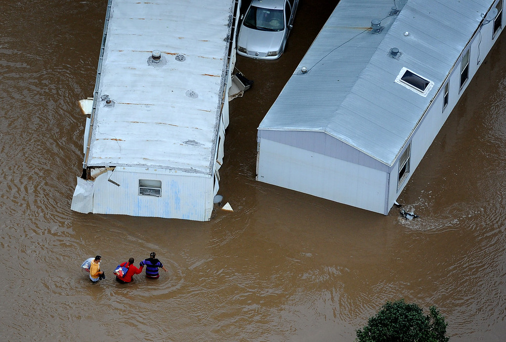 Description of . People walk through waist deep water in a trailer park off of 37th street in Evans Colorado, carrying belongings recovered from flooded  homes in the area. Aerial photographs of the Platte River flooding cities and farms in Weld County Colorado. (Photo By Tim Rasmussen/The Denver Post)