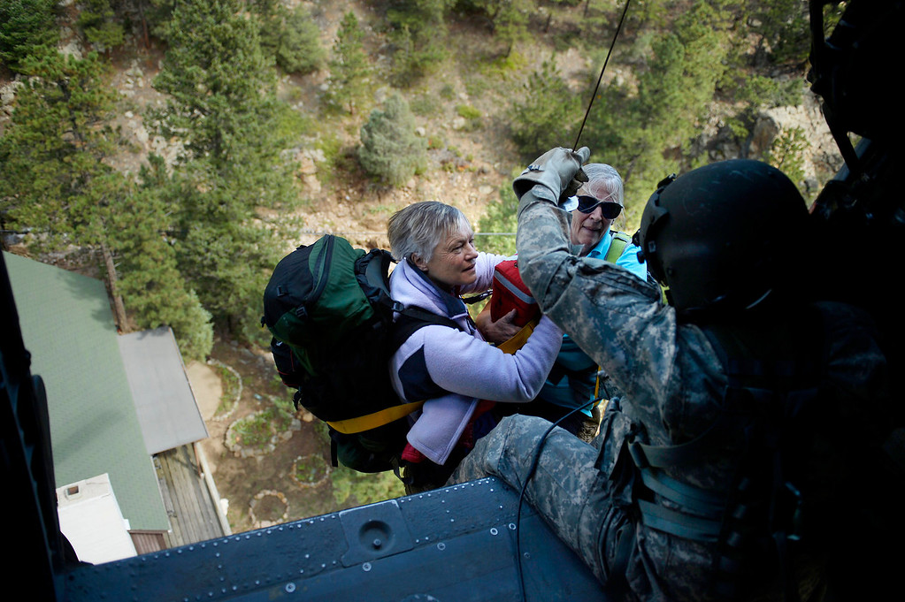 Description of . Two women are hoisted into a UH-60 Black Hawk by Sgt 1st class Keith Bart near Jamestown during a search and rescue flight with members of the 2-4 GSAB with the 4th ID of Fort Carson September 17, 2013 Boulder, CO. (Photo By Joe Amon/The Denver Post)