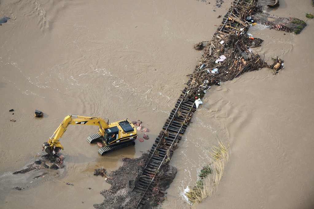 Description of . Crews work to clear debris from flooded railroad tracks in Loveland Colorado Saturday morning, September 14, 2013. (Photo By Andy Cross/The Denver Post)