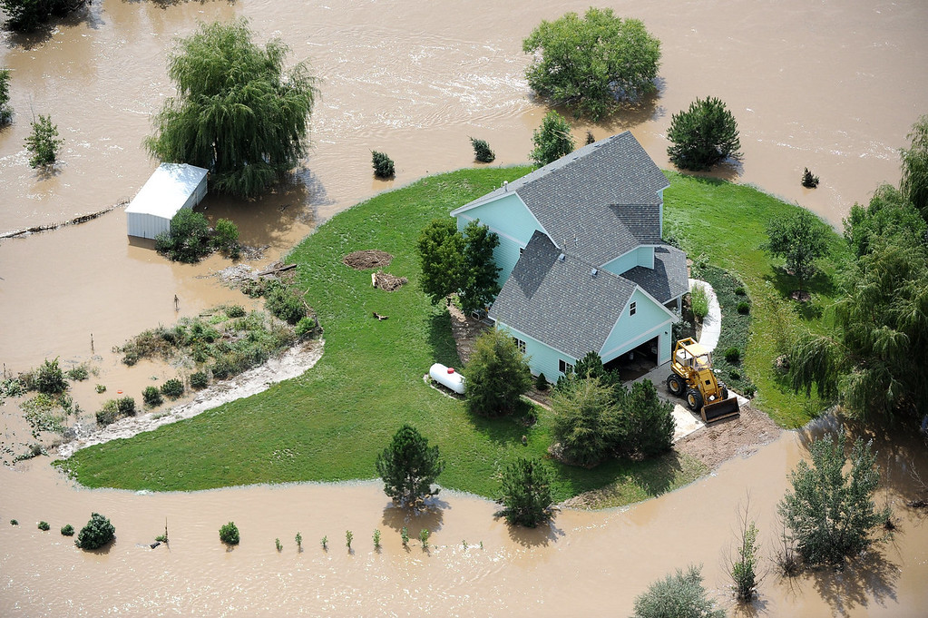 Description of . A home near Evans is surrounded by flood waters from the South Platte River. Aerial photographs of the Platte River flooding cities and farms in Weld County Colorado. (Photo By Tim Rasmussen/The Denver Post)