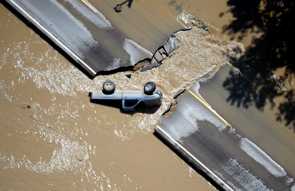 Description of . A truck lays on its side in the floodwaters on a breached section of a road near Longmont on Monday, September 16, 2013. (Photo By Tim Rasmussen/The Denver Post)