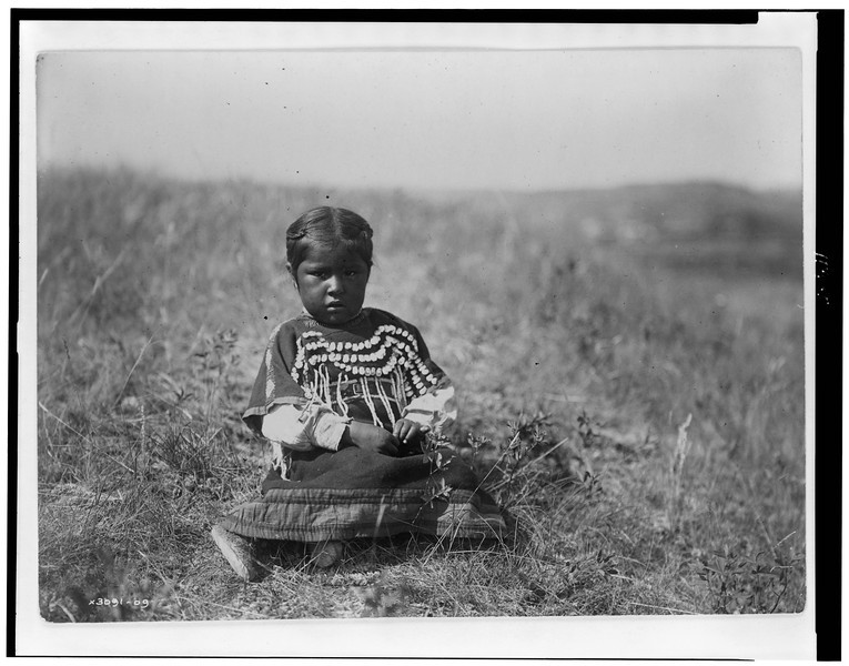 Description of  Title: Running Owl's daughter.  <br />Date Created/Published: c1910.  <br />Summary: Young Piegan girl, full-length portrait, wearing dress decorated with elk teeth, sitting on open ground, facing front.  <br />Photograph by Edward S. Curtis, Curtis (Edward S.) Collection, Library of Congress Prints and Photographs Division Washington, D.C.