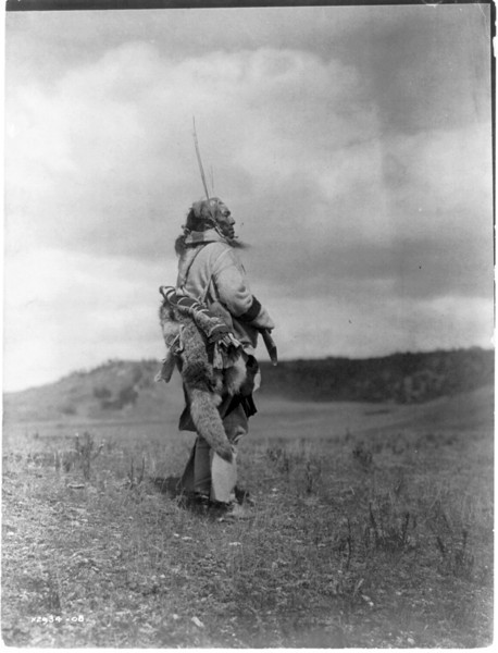 Description of  Title: The scout--Atsina.  <br />Date Created/Published: c1908 November 19.  <br />Summary: Atsina man, full-length portrait, standing, turned right, holding rifle while he looks over a grassy plain.  <br />Photograph by Edward S. Curtis, Curtis (Edward S.) Collection, Library of Congress Prints and Photographs Division Washington, D.C.