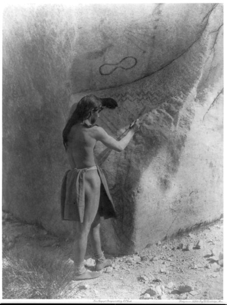 Description of  Title: The primitive artists--Paviotso.  <br />Date Created/Published: c1924 August 5.  <br />Summary: Paviotso man standing, marking side of glacial boulder that already has petroglyphs on it.  <br />Photograph by Edward S. Curtis, Curtis (Edward S.) Collection, Library of Congress Prints and Photographs Division Washington, D.C.