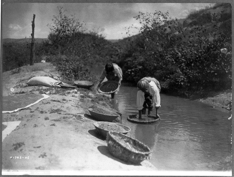 Description of  Title: Washing wheat--San Juan.  <br />Date Created/Published: c1905 December 26.  <br />Summary: Two San Juan Indians dipping baskets of wheat into an acequia, or irrigation ditch, to dissolve dirt and to float away debris from the wheat kernels.  <br />Photograph by Edward S. Curtis, Curtis (Edward S.) Collection, Library of Congress Prints and Photographs Division Washington, D.C.
