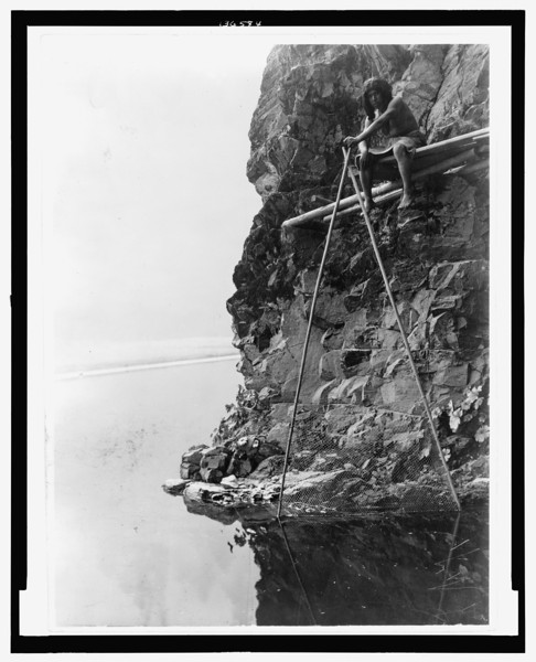 Description of  Title: Fishing platform on Trinity River--Hupa.  <br />Date Created/Published: c1923 Jun. 30.  <br />Summary: Photograph shows a Hupa man sitting on a platform on a rocky cliff, handling a fishing net.  <br />Photograph by Edward S. Curtis, Curtis (Edward S.) Collection, Library of Congress Prints and Photographs Division Washington, D.C.