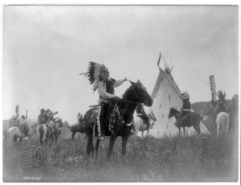 Description of  Title: Village herald.  <br />Date Created/Published: c1907 December 26.  <br />Summary: Dakota man, wearing war bonnet, sitting on horseback, his left hand outstreched toward tipi in background, others on horseback.  <br />Photograph by Edward S. Curtis, Curtis (Edward S.) Collection, Library of Congress Prints and Photographs Division Washington, D.C.
