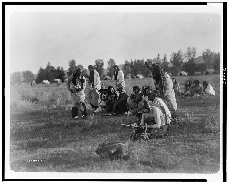 Description of  Title: Priests passing before the pipe--Cheyenne.  <br />Date Created/Published: c1910.  <br />Summary: Group of Cheyenne people, most seated in a semicircle during sun dance ceremony, woman in foreground is holding pipe, buffalo skull in foreground.  <br />Photograph by Edward S. Curtis, Curtis (Edward S.) Collection, Library of Congress Prints and Photographs Division Washington, D.C.