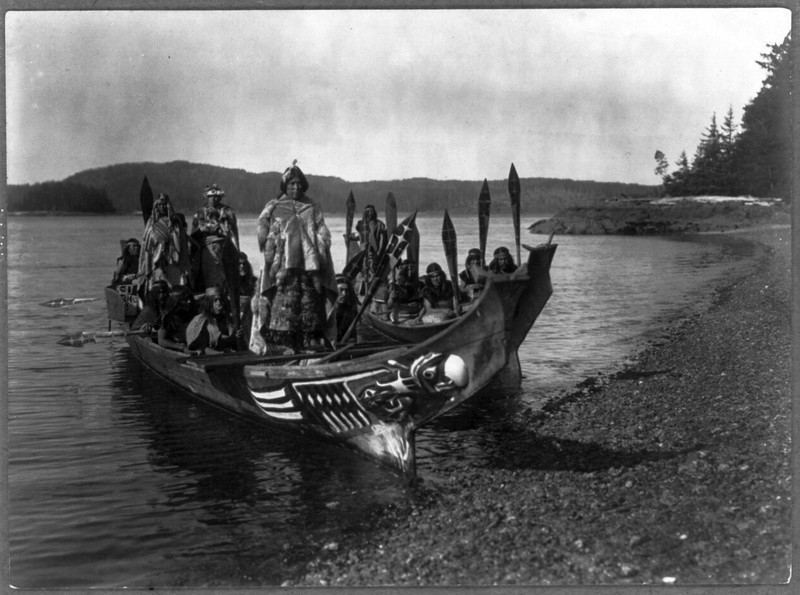 "Description of  Title: The wedding party--Qagyuhl.  <br />Date Created/Published: c1914 November 13.  <br />Summary: Two canoes pulled ashore with wedding party, bride and groom standing on ""bride's seat"" in the stern, relative of the bride dances on platform in bow.  <br />Photograph by Edward S. Curtis, Curtis (Edward S.) Collection, Library of Congress Prints and Photographs Division Washington, D.C."