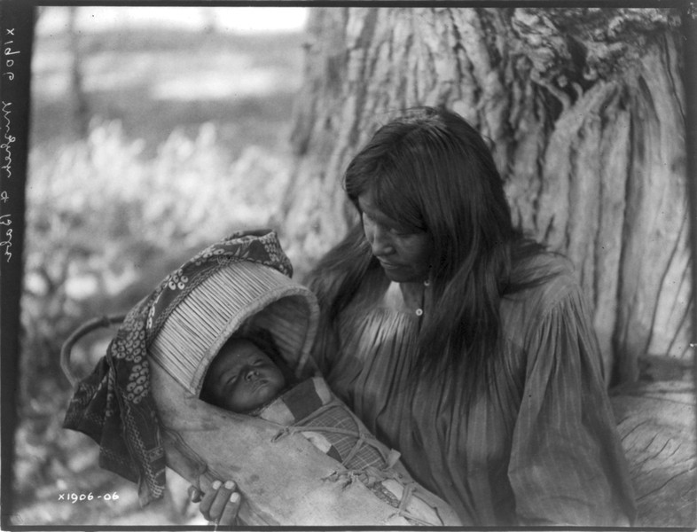 Description of  Title: Mizheh and babe.  <br />Date Created/Published: c1906 December 19.  <br />Summary: Apache woman, at base of tree, holding infant in cradleboard in her lap.  <br />Photograph by Edward S. Curtis, Curtis (Edward S.) Collection, Library of Congress Prints and Photographs Division Washington, D.C.