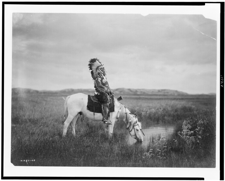 Description of  Title: An oasis in the Badlands.  <br />Date Created/Published: c1905.  <br />Summary: Oglala man (Red Hawk) on horse drinking at oasis.  <br />Photograph by Edward S. Curtis, Curtis (Edward S.) Collection, Library of Congress Prints and Photographs Division Washington, D.C.