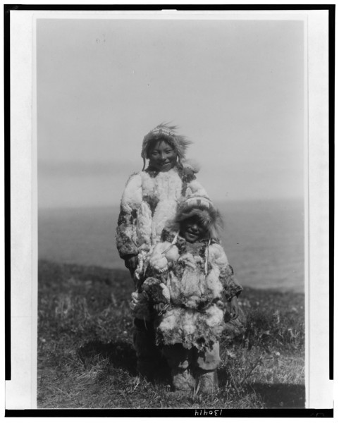Description of  Title: Duck-skin parkas, Nunivak  <br />Date Created/Published: c1929 Feb. 28.  <br />Summary: Eskimo adult and child wearing duck-skin parkas.  <br />Photograph by Edward S. Curtis, Curtis (Edward S.) Collection, Library of Congress Prints and Photographs Division Washington, D.C.