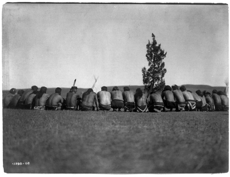 Description of  Title: Arikara medicine fraternity--The prayer.  <br />Date Created/Published: c1908 November 19.  <br />Summary: Arikara shamans, without shirts, backs to camera, seated in a semi-circle around a sacred cedar tree, tipis in background.  <br />Photograph by Edward S. Curtis, Curtis (Edward S.) Collection, Library of Congress Prints and Photographs Division Washington, D.C.