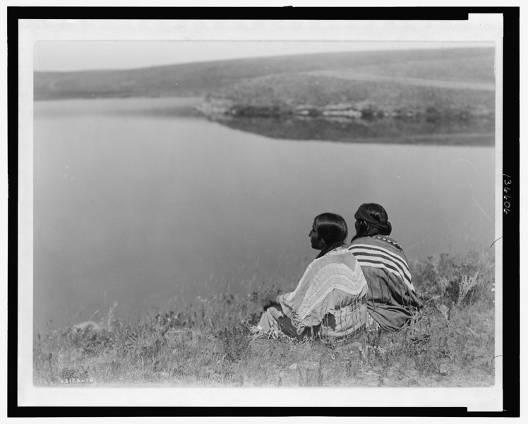 Description of  Title: An idle hour, Piegan.  <br />Date Created/Published: c1910 December 8.  <br />Summary: Photograph shows two Piegan Indians sitting on grassy area above a body of water.  <br />Photograph by Edward S. Curtis, Curtis (Edward S.) Collection, Library of Congress Prints and Photographs Division Washington, D.C.