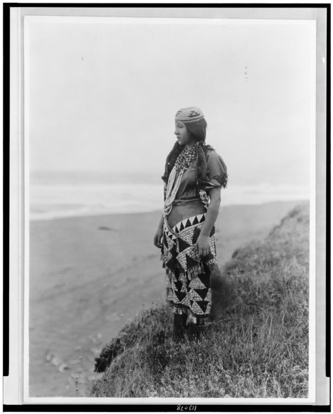 Description of  Title: Woman's primitive dress--Tolowa.  <br />Date Created/Published: c1923.  <br />Summary: Ada Lopez Richards, full-length portrait, standing near the shore wearing hat, necklaces, and dress.  <br />Photograph by Edward S. Curtis, Curtis (Edward S.) Collection, Library of Congress Prints and Photographs Division Washington, D.C.