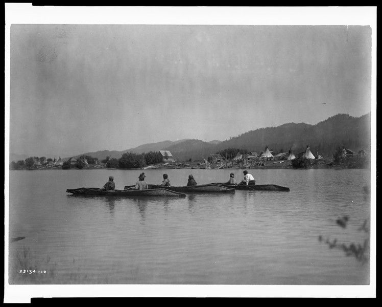 Description of  Title: Home of the Kalispel.  <br />Date Created/Published: c1910 March 11.  <br />Summary: Kalispel camp on a riverbank with tipis and frame houses, three canoes in water in foreground.  <br />Photograph by Edward S. Curtis, Curtis (Edward S.) Collection, Library of Congress Prints and Photographs Division Washington, D.C.
