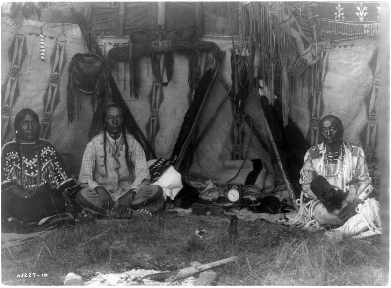 Description of  Title: In a Piegan lodge.  <br />Date Created/Published: c1910 March 11.  <br />Summary: Little Plume and son Yellow Kidney seated on ground inside lodge, pipe between them.  <br />Photograph by Edward S. Curtis, Curtis (Edward S.) Collection, Library of Congress Prints and Photographs Division Washington, D.C.