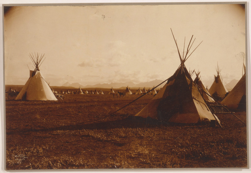 Description of  Title: Piegan encampment.  <br />Date Created/Published: c1900.  <br />Summary: Tepees with mountains in background.  <br />Photograph by Edward S. Curtis, Curtis (Edward S.) Collection, Library of Congress Prints and Photographs Division Washington, D.C.