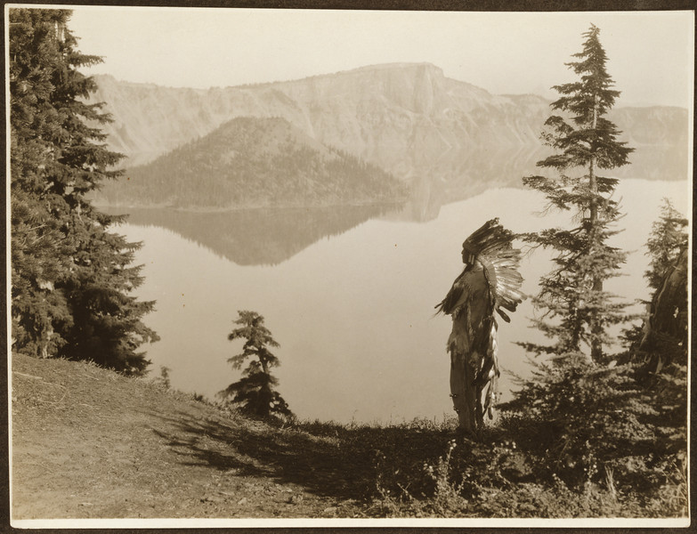 Description of  Title: The chief--Klamath.  <br />Date Created/Published: c1923.  <br />Summary: Photograph shows Klamath Indian chief in ceremonial headdress standing on hill overlooking lake, California or Oregon.  <br />Photograph by Edward S. Curtis, Curtis (Edward S.) Collection, Library of Congress Prints and Photographs Division Washington, D.C.