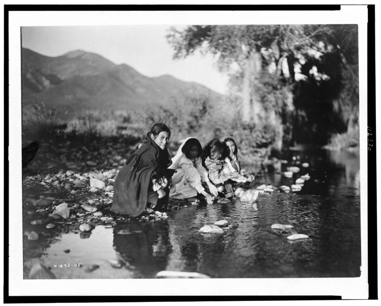 Description of  Title: Taos children.  <br />Date Created/Published: c1905.  <br />Summary: Four Taos children squat on rocks at edge of stream, mountains in background.  <br />Photograph by Edward S. Curtis, Curtis (Edward S.) Collection, Library of Congress Prints and Photographs Division Washington, D.C.